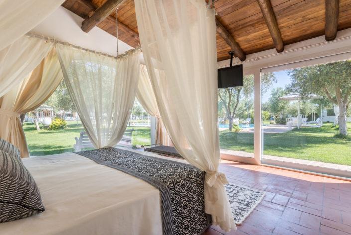 Camera da letto con bellissima vista sul giardino. Fotografia di interni realizzata nel Ristorante Locanda Da Renzo, provincia di Oristano