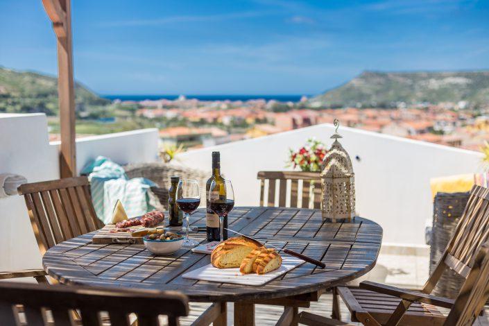 Aperitivo su una terrazza panoramica a Bosa. Fotografia per il settore immobiliare in Sardegna