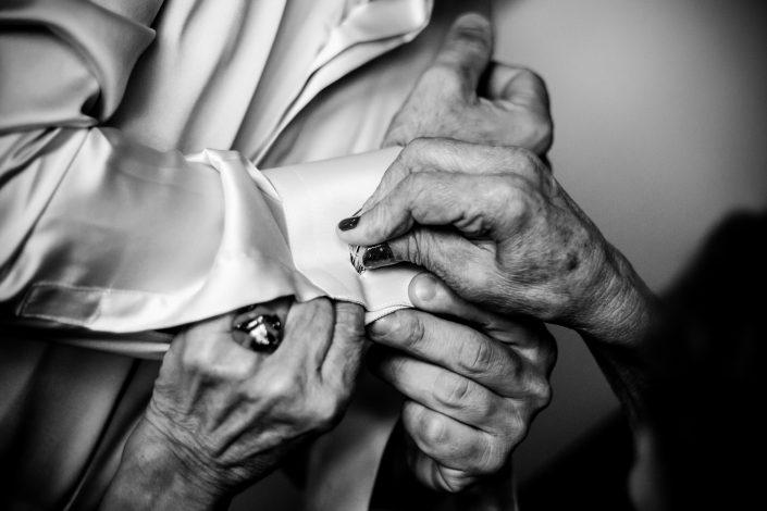 Dettagli di Matrimonio. La madre aiuta il figlio a vestirsi.