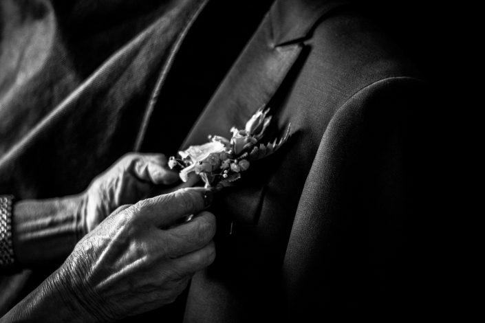 Dettagli di Matrimonio in bianco e nero. Le mani della madre dello sposo che si occupa degli ultimi ritocchi